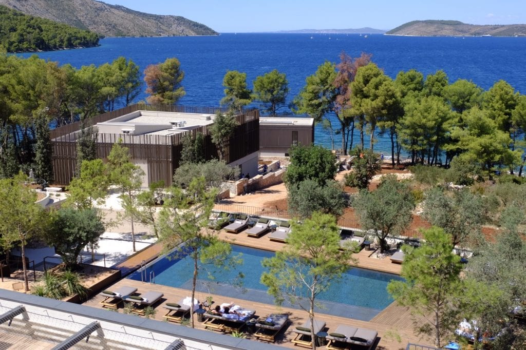 Maslina Resort: a view from above of a rectangular pool edged with seats, and a tree-edged shoreline and bright blue water.