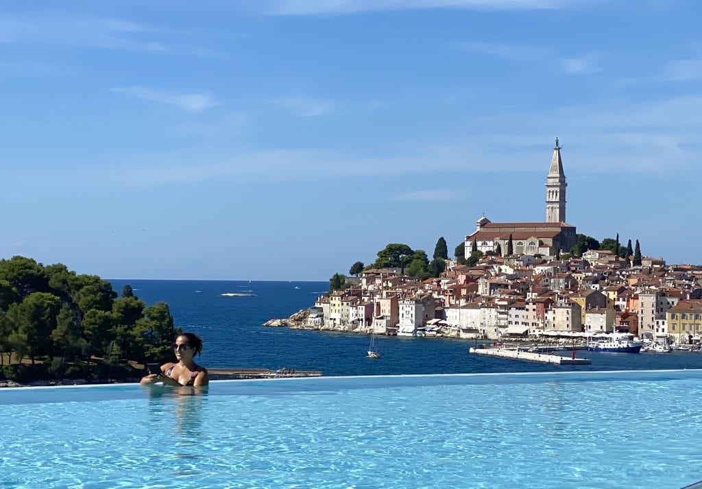 Kate reading her Kindle in an infinity pool overlooking the church-topped city of Rovinj in the distance, at the Grand Park Hotel.
