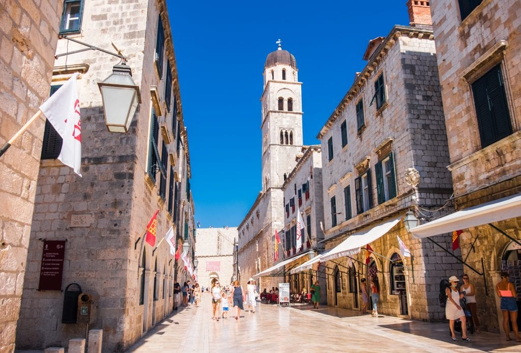 Empty polished streets in the old town of Dubrovnik, underneath a bright blue sky.
