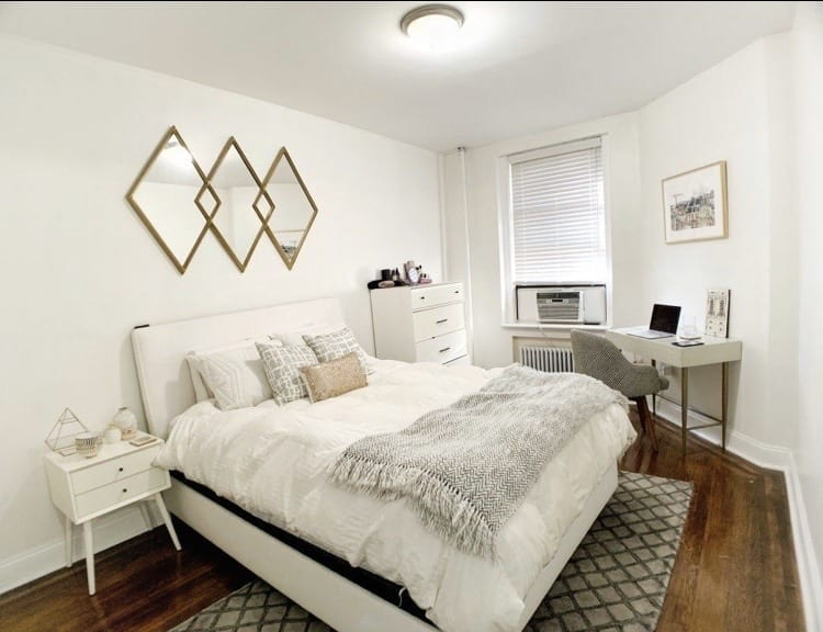 Kate's New York bedroom: a large white bed with a white bedspread, silver and gold pillows, a gray and white blanket, white nightstand, dresser, and small desk, gray rug, gray and white striped office chair, and gold mirror shaped with three diamonds hanging above the bed.