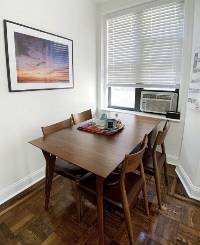 Kate's dark wood dining table and four wooden chairs with dark red leather seats.