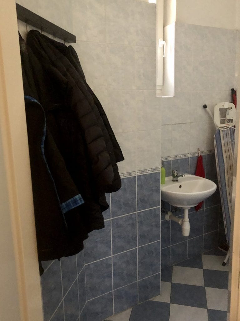 Black jackets hanging on a rack in the bathroom.