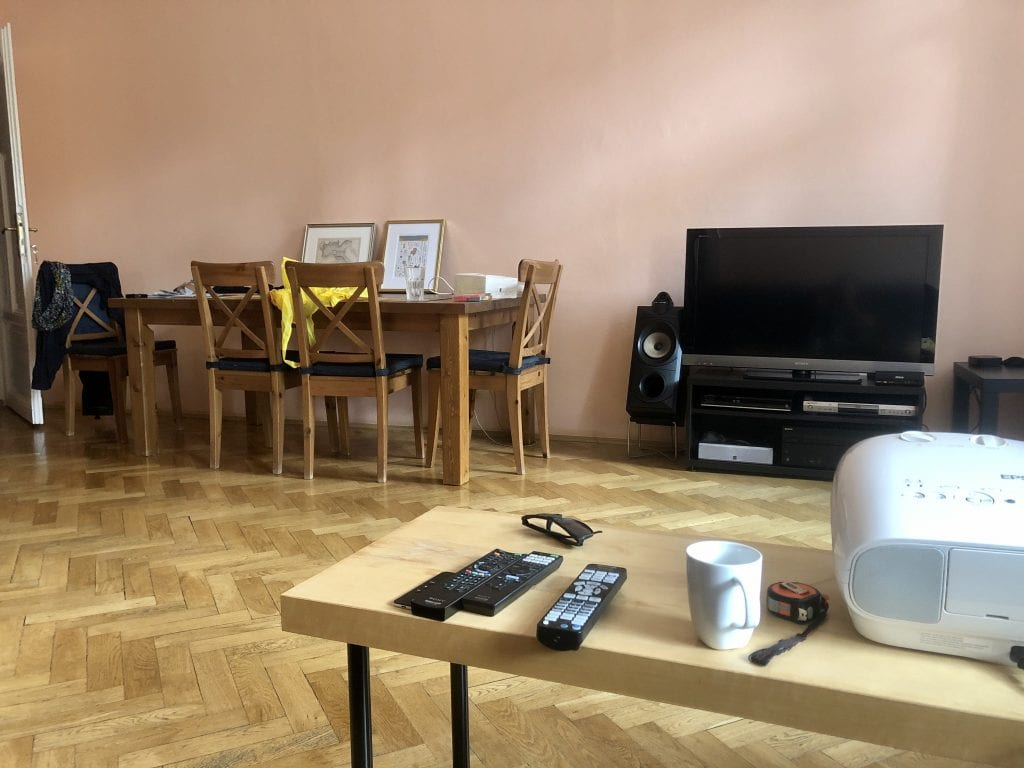 The same room from another angle: IKEA plastic table in foreground, dining table and TV in background.