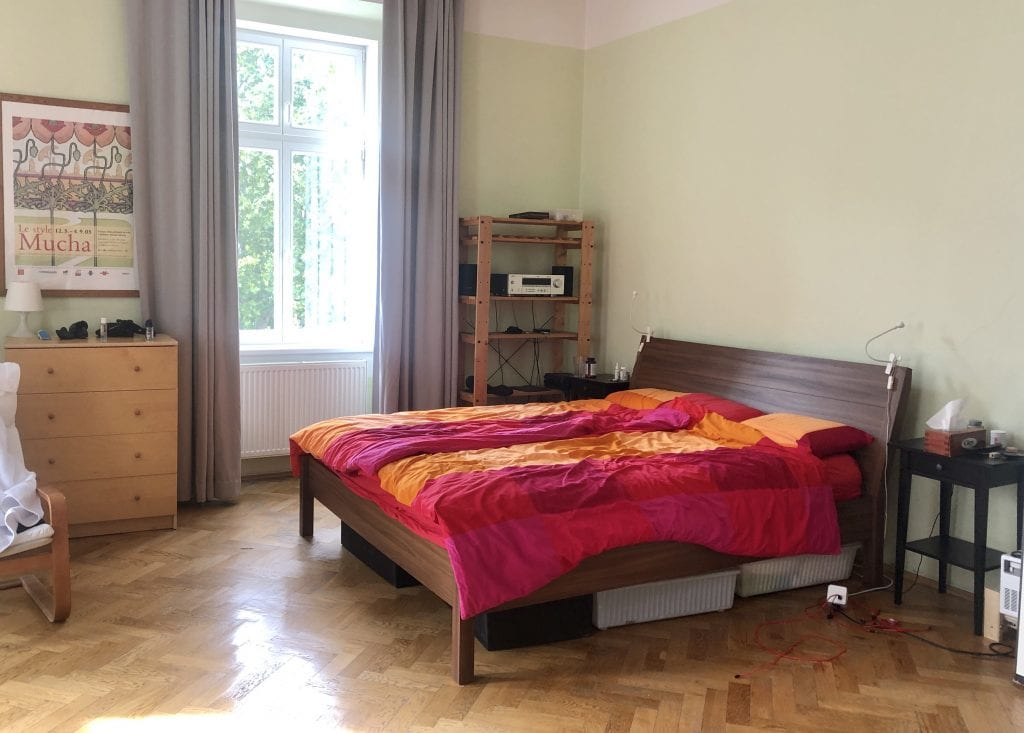 A wooden bed covered with a blocky red pink and orange IKEA bedspread, open shelving and dresser in the background.