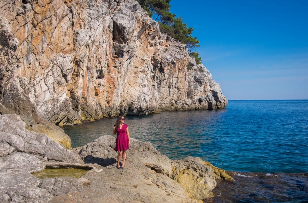 Kate standing on the edge of the rocky coastline in Dubrovnik, wearing a red dress and sunglasses, looking out to sea.