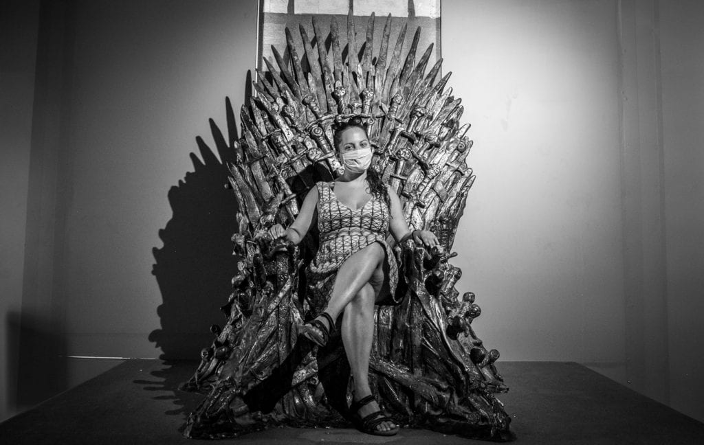 Kate sitting on the Iron Throne from Game of Thrones, wearing a mask and smiling with her eyes.
