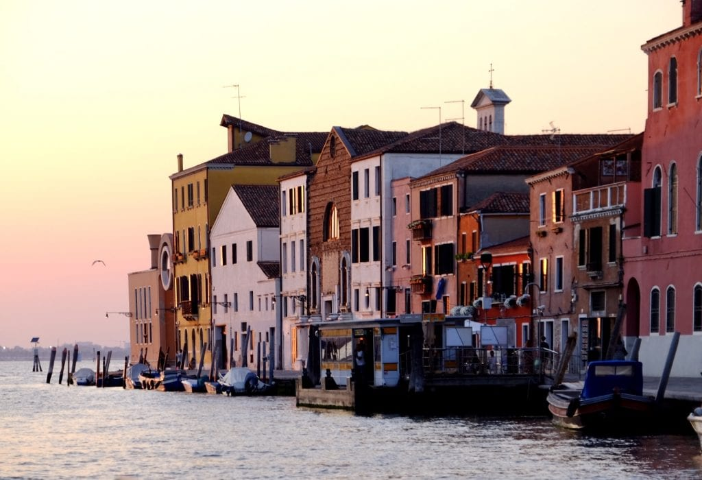 View from a canal of Venetian homes built along the water, turning a pink shade at sunset.