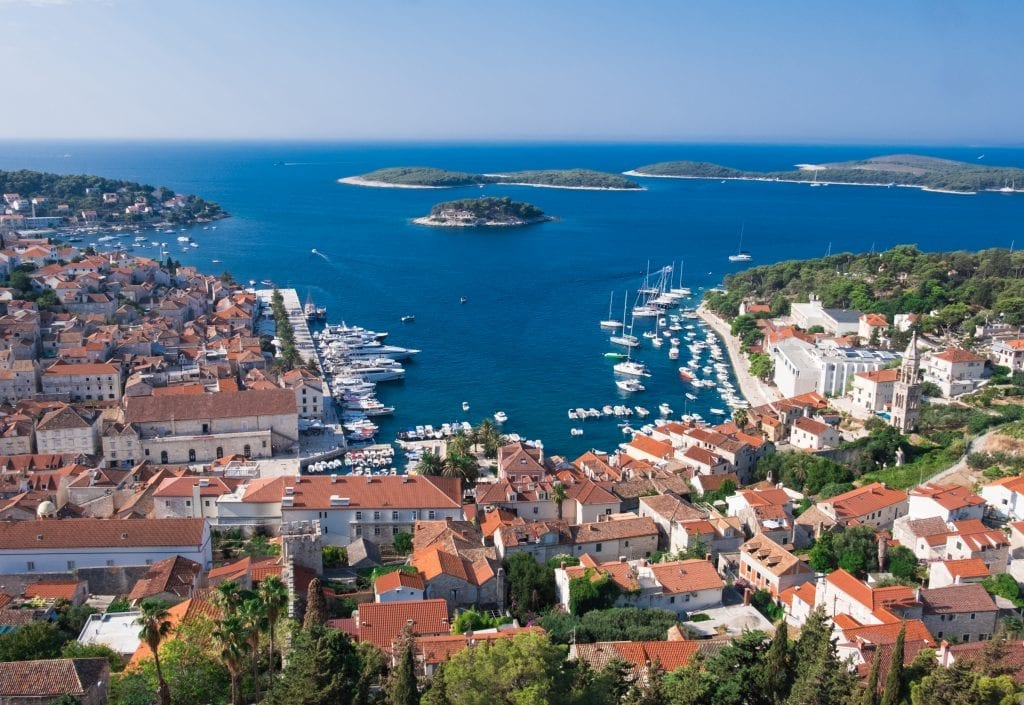 View of Hvar Town from the Spanish Fortress: a view from above, you see a small harbor surrounded with white buildings topped with orange roofs. In the distance are the green Pakleni Islands.