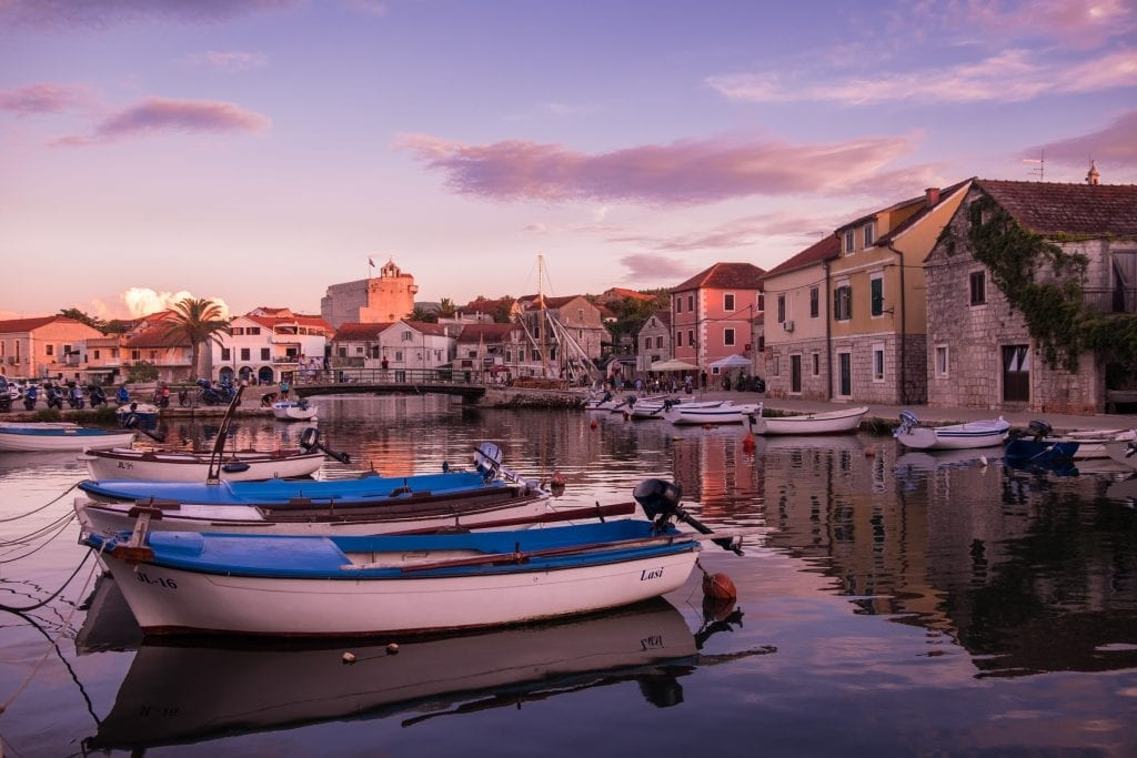 Vrboska village at sunset: the sky is lit in purple and there are small boats in the canal, surrounded by stone houses on each side.