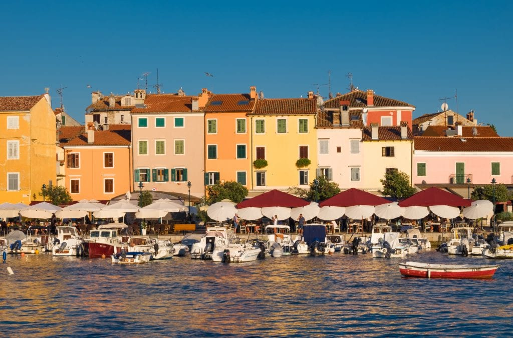Cafes along the waterfront in Rovinj underneath umbrellas; bright yellow buildings with orange roofs behind them.