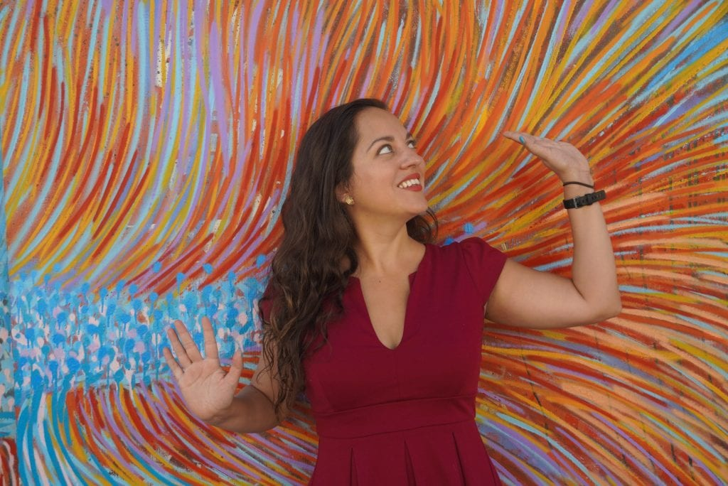 Kate posing with her arms in the air in front of a mural of many different colors in an abstract design.