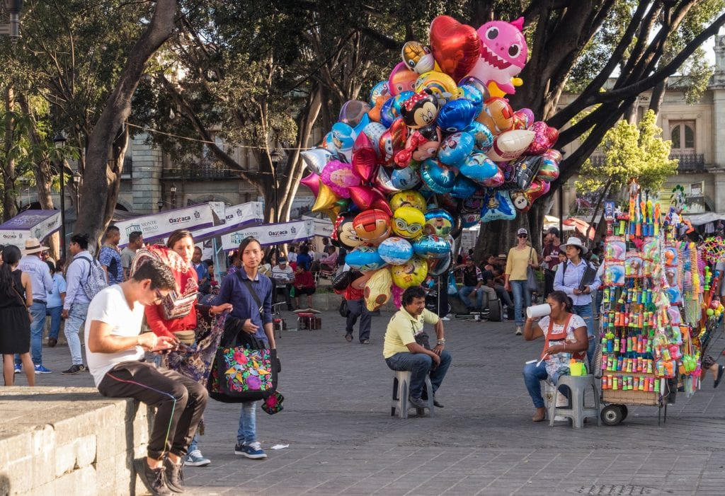 People walking down the main square of Oaxaca, the zocalo. One man carries a huge bundle of balloons; other people are sitting and looking at their phones.