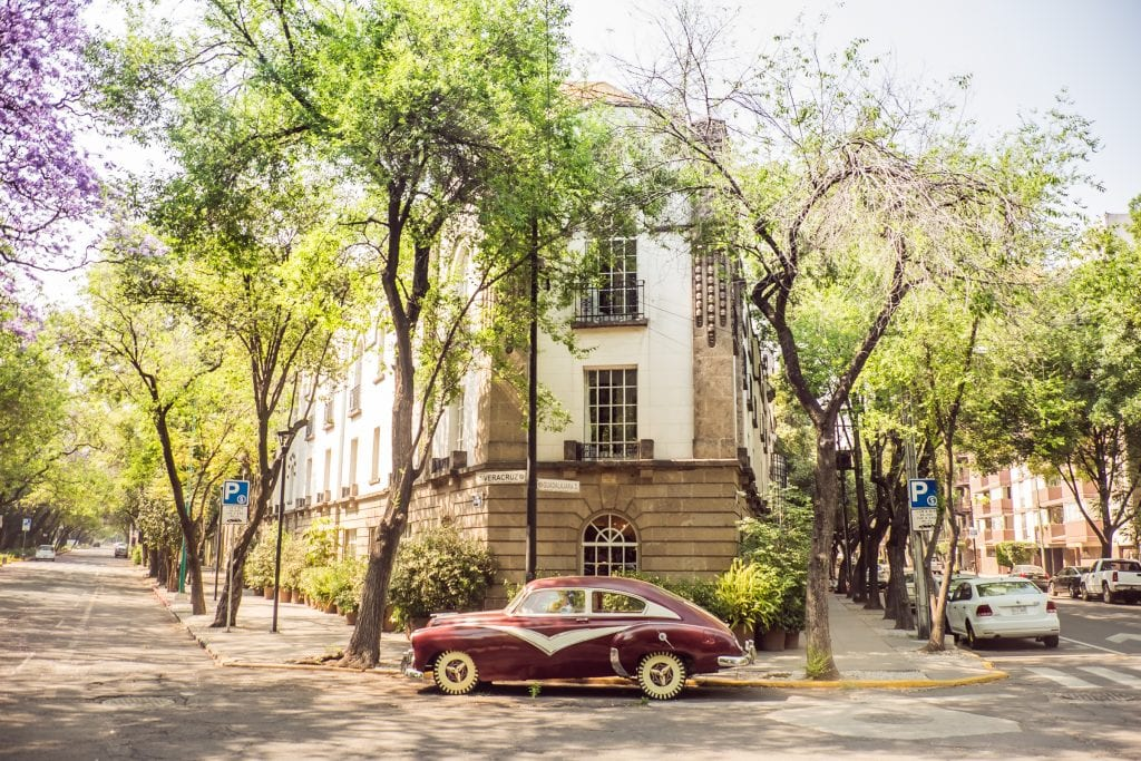 An old-fashioned maroon car parked in front of a white building with two streets on each side of it, lined with jacaranda trees.