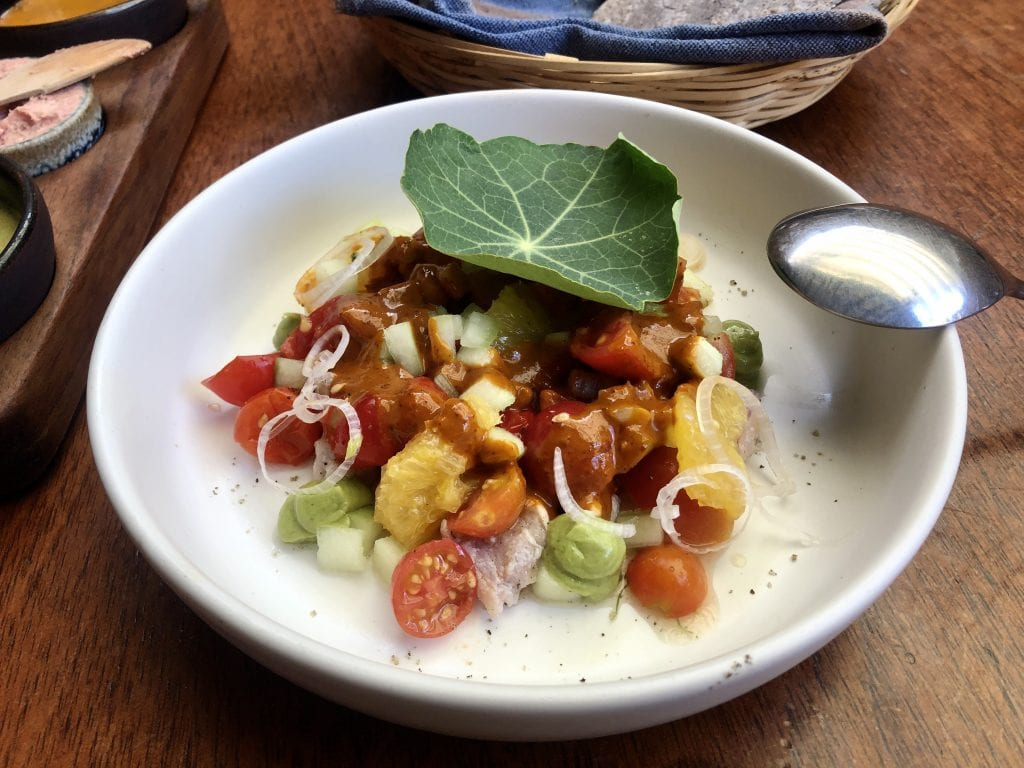A fancy plate of Oaxaca food -- it looks like ceviche mixed with vegetables and a large green leaf on top.