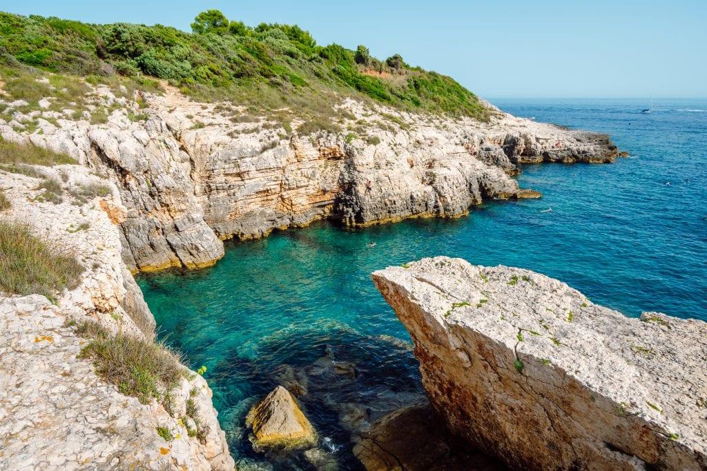 Jagged cliffs jutting into the bright teal ocean in Kamenjak, Croatia