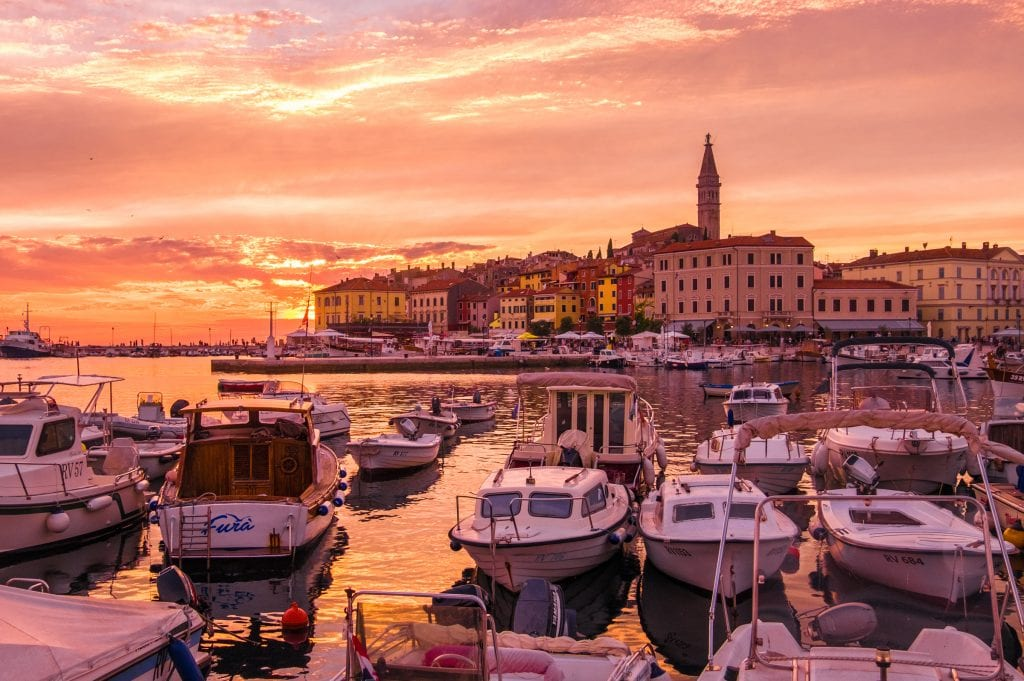 Rovinj at sunset: The whole sky is lit up orange and yellow. In the foreground are rows of small white boats docked up; in the back is the old city of Rovinj on the edge of the water, a big church tower sticking out of the top.