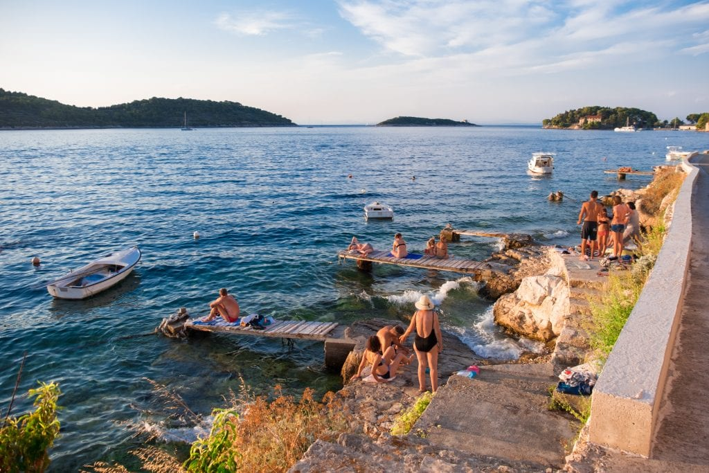 Several people lounging on narrow wooden plant docks jutting into the bright blue sea in Vis. Some small rowboats are in the water.
