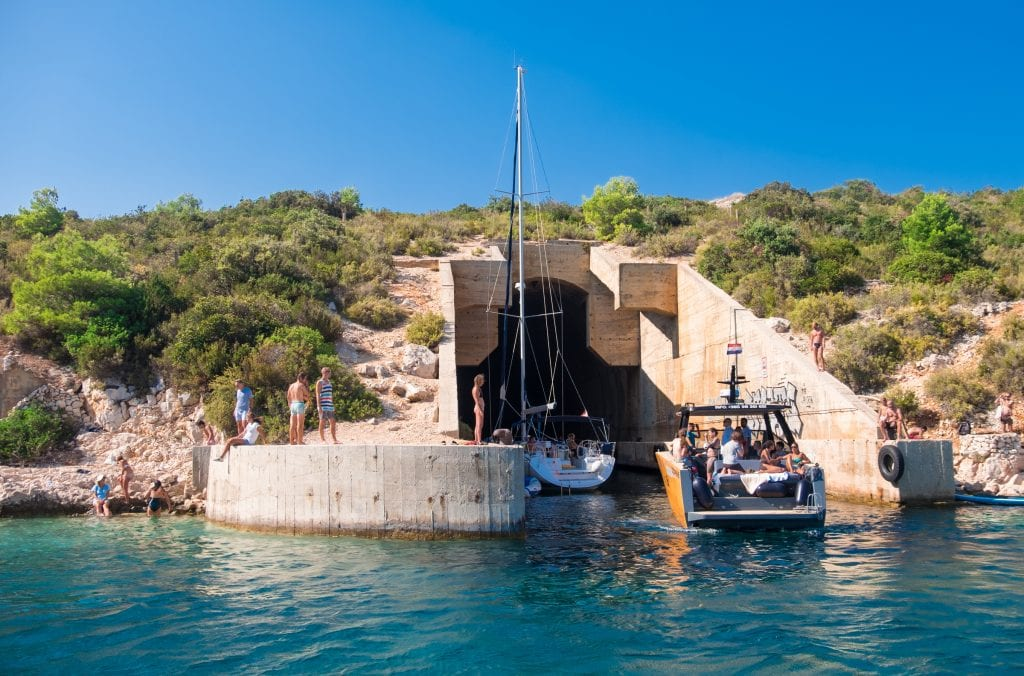 A submarine tunnel coming out of a hill in Vis, emerging into the ocean. Sailboats are sailing into the tunnel and people hang out on either sides of the tunnel.
