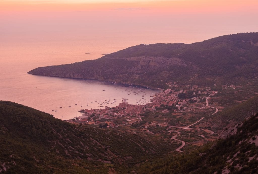 A pink sunset from the top of Hum Mountain, overlooking mountaintops and the town of Komiza in front of the sea below.