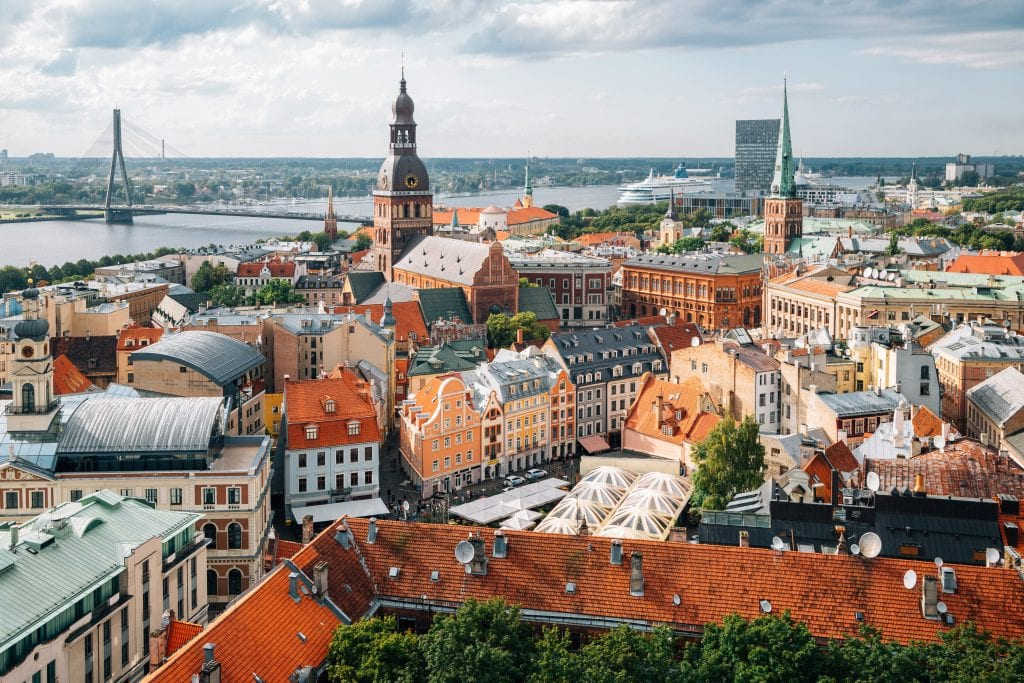A skyline view of Riga: small Art Nouveau buildings in the foreground, a church tower and a bridge in the background. In the back is a river, and there seems to be a large cruise ship on it.