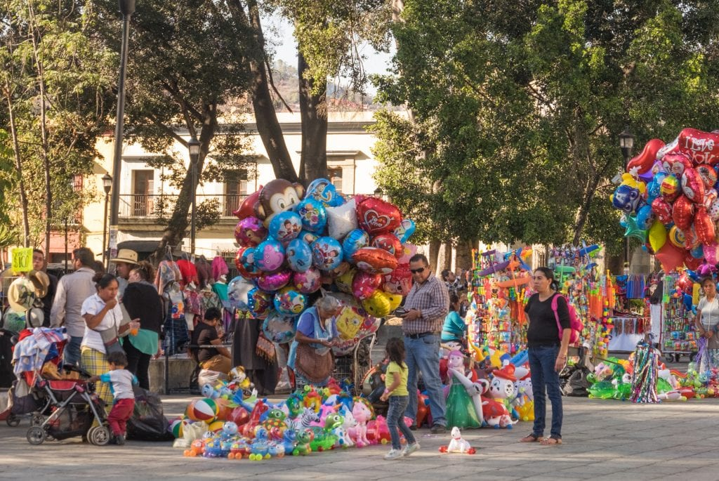 A shot from the Zocalo: a man buying a balloon for his four-year-old daughter as her mother looks on.