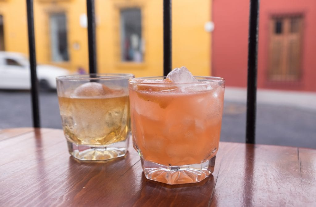 Two cocktails on a wooden shelf: one pale yellow and one pinkish orange, filled with large ice cubes.