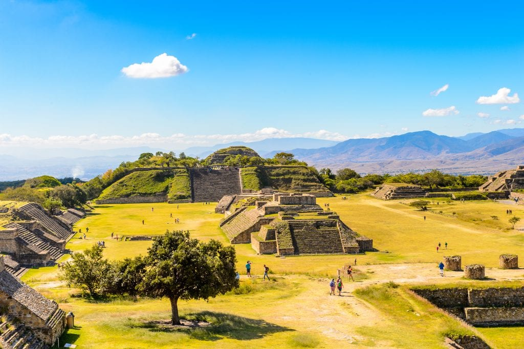 The Monte Alban ruins: several flap-topped stone pyramids, many of them topped with vegetation.
