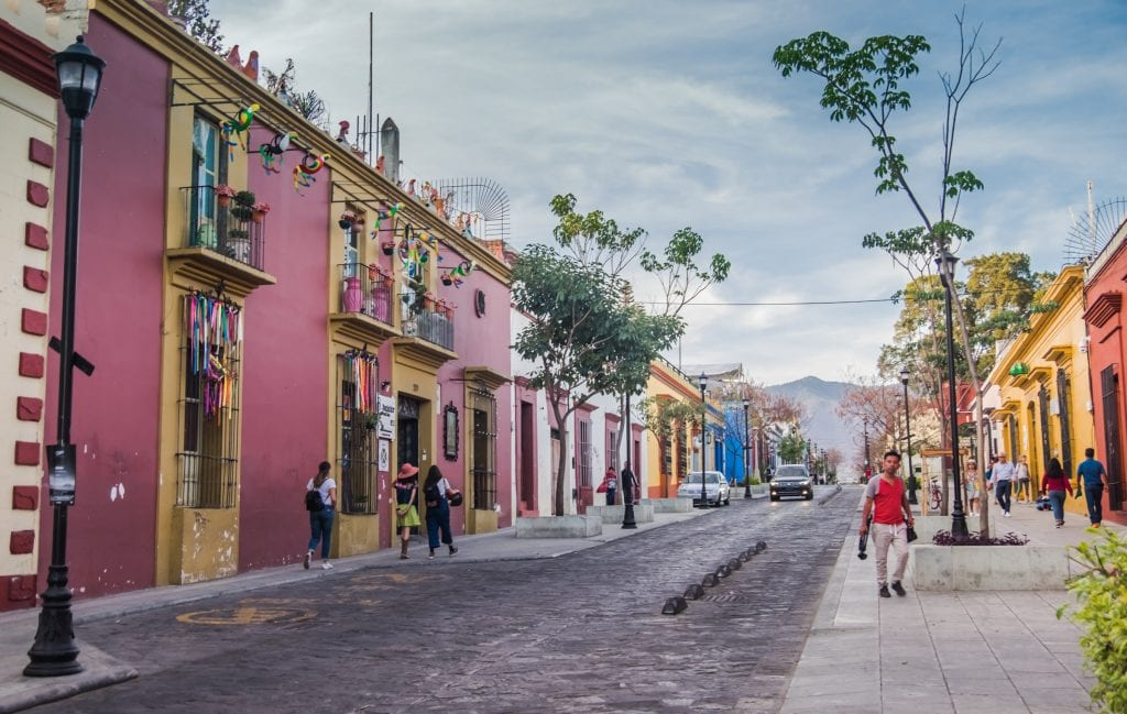 A bright and colorful street in Oaxaca with purple, yellow, blue, and white buildings in a row. There are trees and you see people walking down the street and mountains rising in the background.