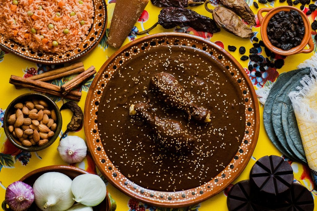 An overhead view of Oaxacan delicacies: Chicken in a dark brown mole sauce topped with sesame seeds, surrounded by chiles, rice, onions, and other spices.