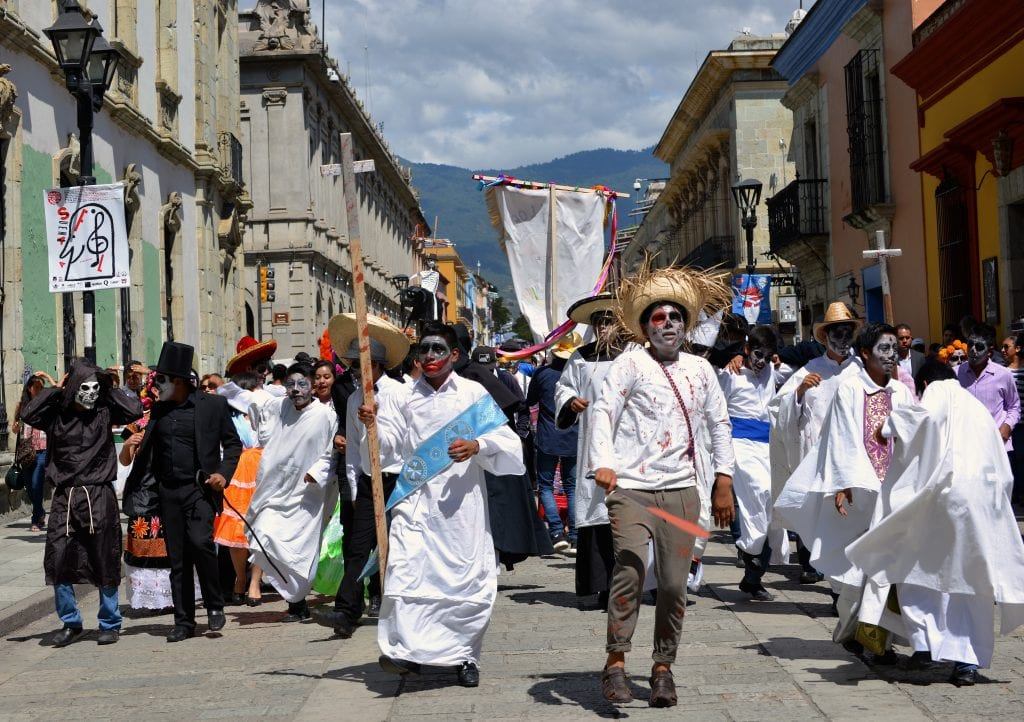 Oaxacan people dressed up in white clothing with zombie-like gray face makeup, parading through the streets for Day of the Dead.