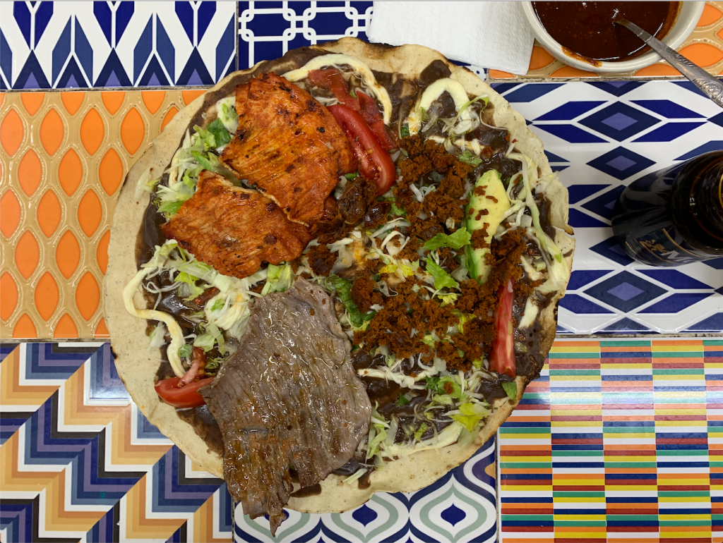 A Oaxacan tlauyda -- a giant tortilla topped with meat and vegetables, served on a blue and orange patterned tile table.