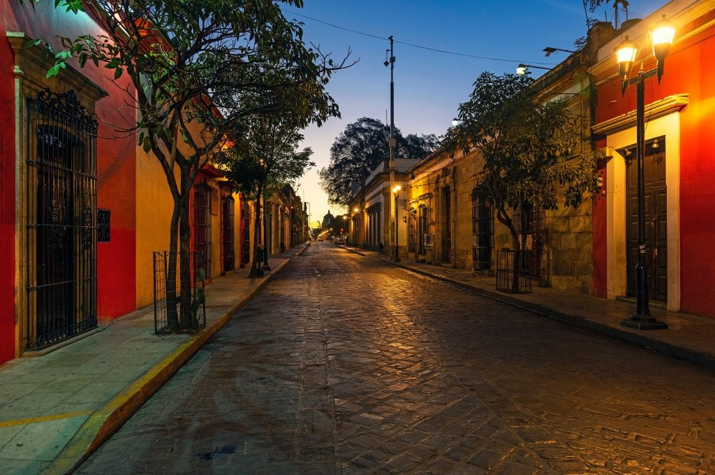Oaxaca at dawn: right red buildings edged with trees, cobblestone street, lamps illuminating the colors, the sky blue and turning yellow.