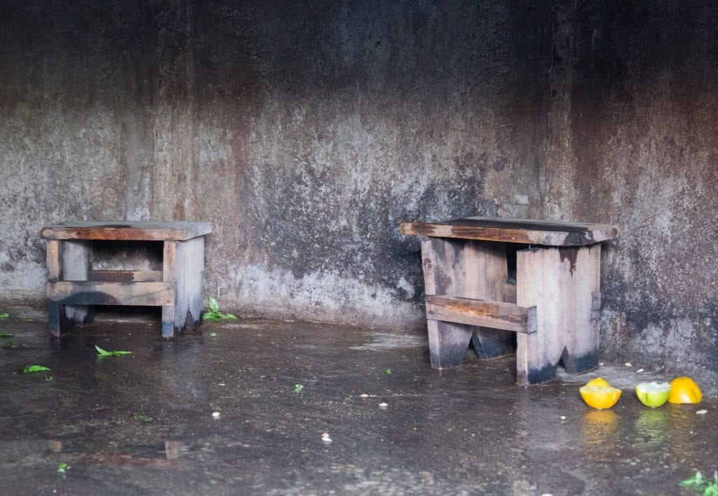 Two benches inside a cave-like setting, with discarded herbs and squeezed halves of oranges in the ground.