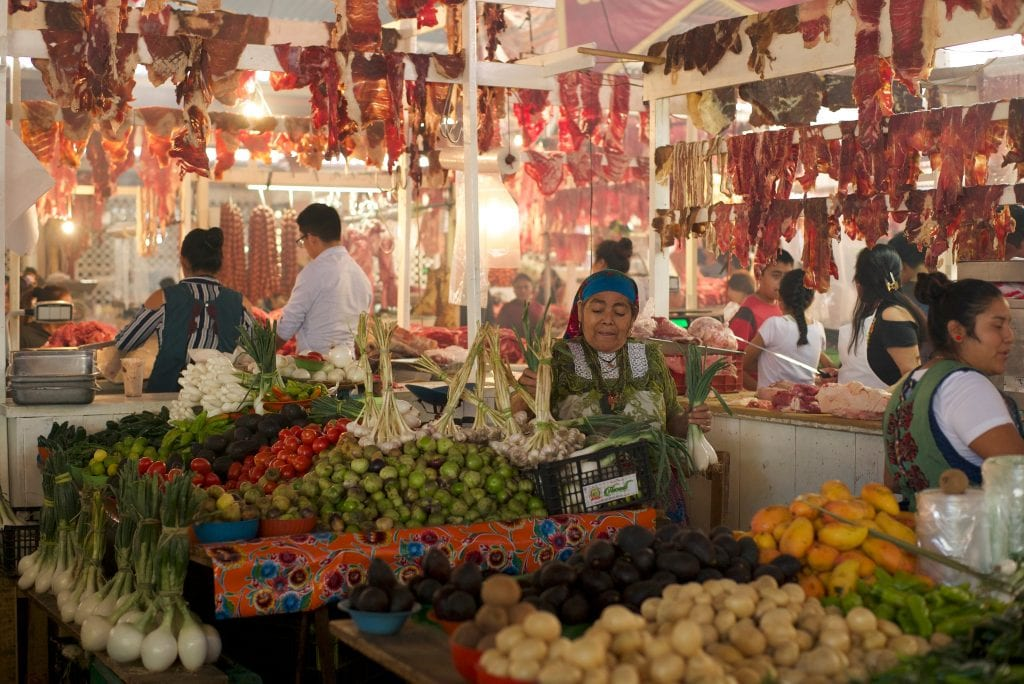 Indigenous women working in a market. There are tables full of fresh produce (limes, peppers, fennel) and raw meat hanging above.
