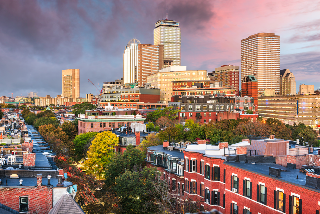 Boston's South End lit up at sunset. You see brownstones on the ground, skyscrapers in the distance, trees turning yellow and orange, and the sky is a pink, purple, and blue sunset.