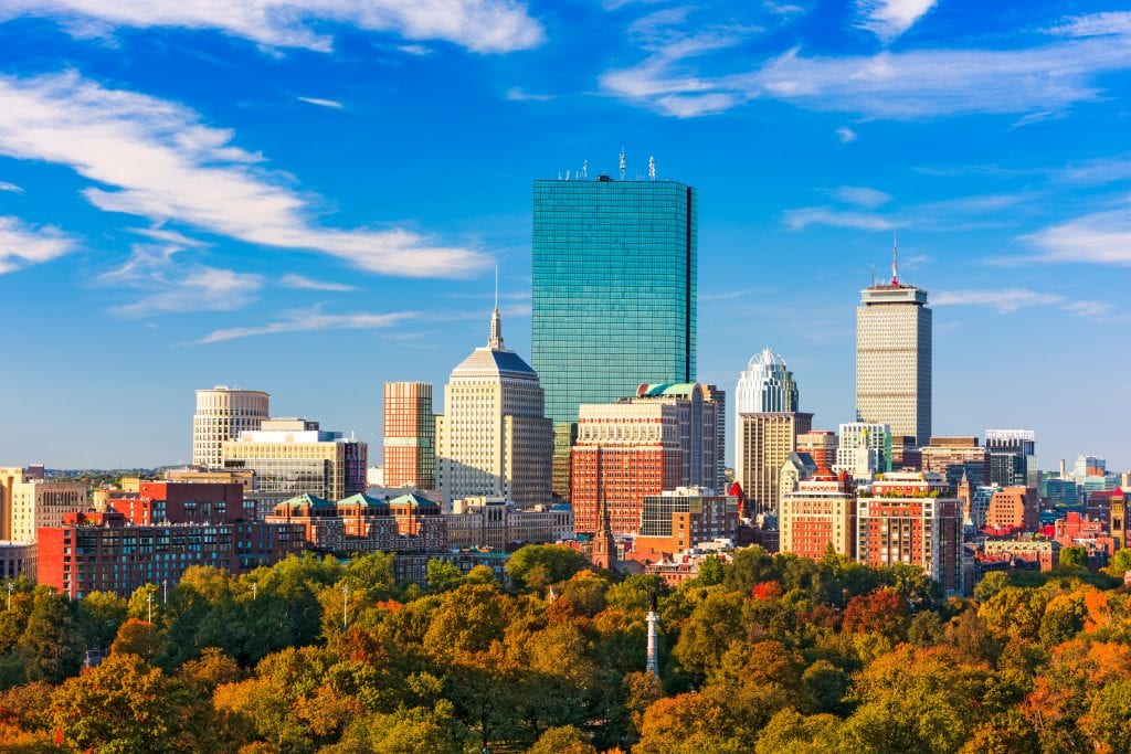 The skyline of Boston underneath a bright blue sky; at the bottom of the buildings are trees turning shades of orange, red, and yellow.