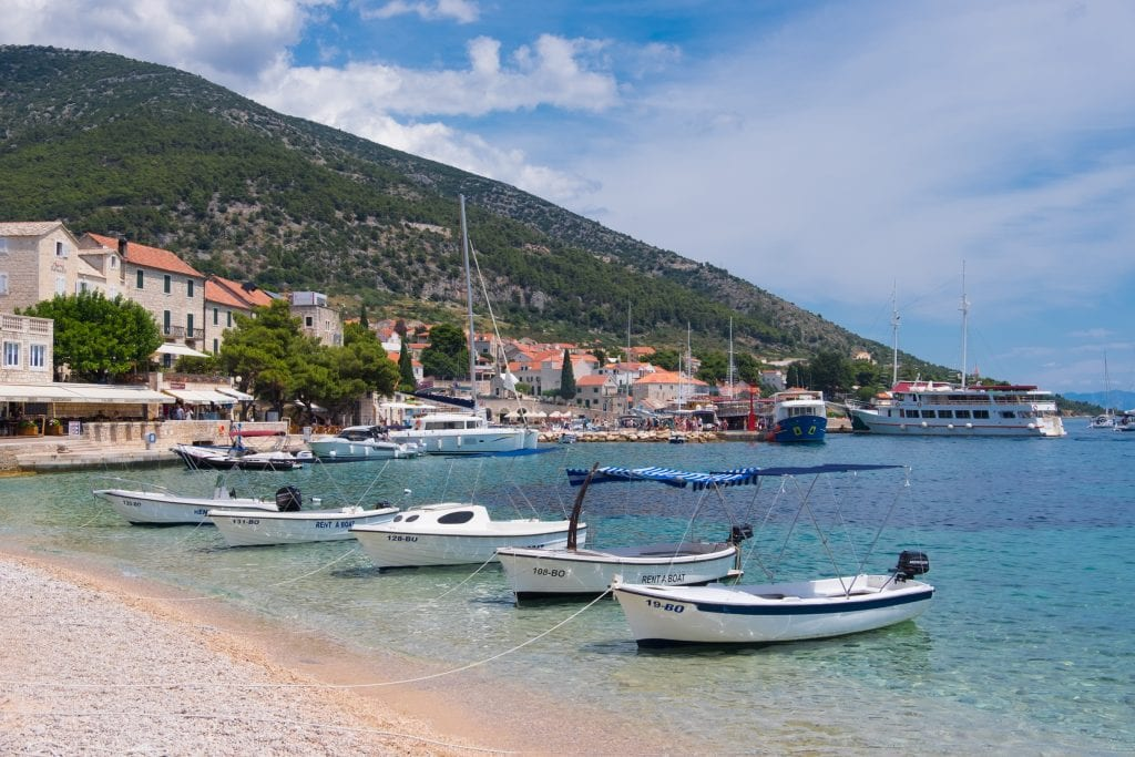 A pebble beach with clear light blue water and several small boats anchored just off shore in Brač, Croatia. In the background you see the white stone buildings of Bol topped with orange roofs.