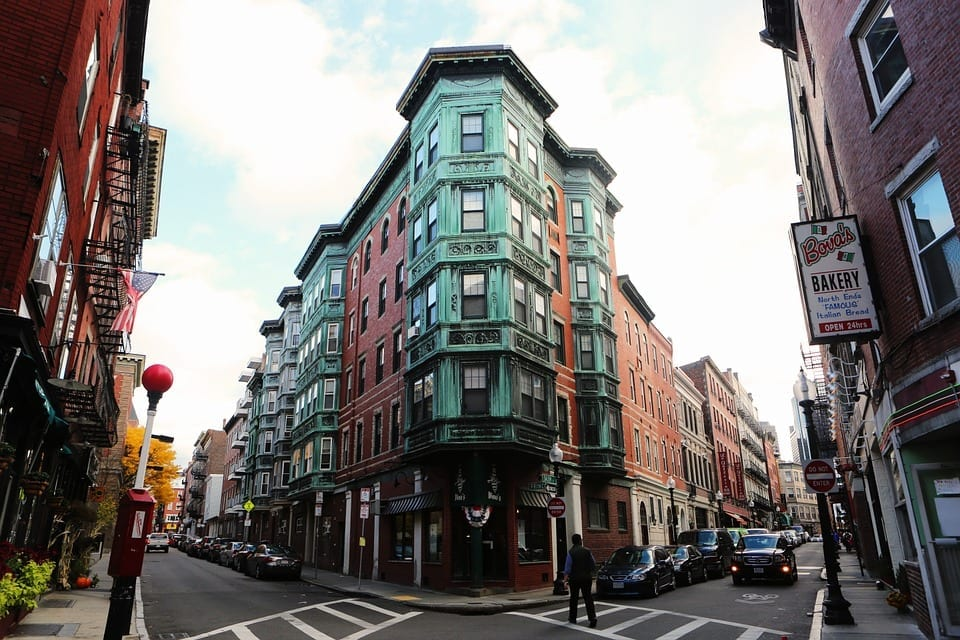 The narrow streets of the North End of Boston. In the middle is a tall brick building with a green metal overlay over the corner, making what looks like bay windows. In the foreground is Bova's Bakery.