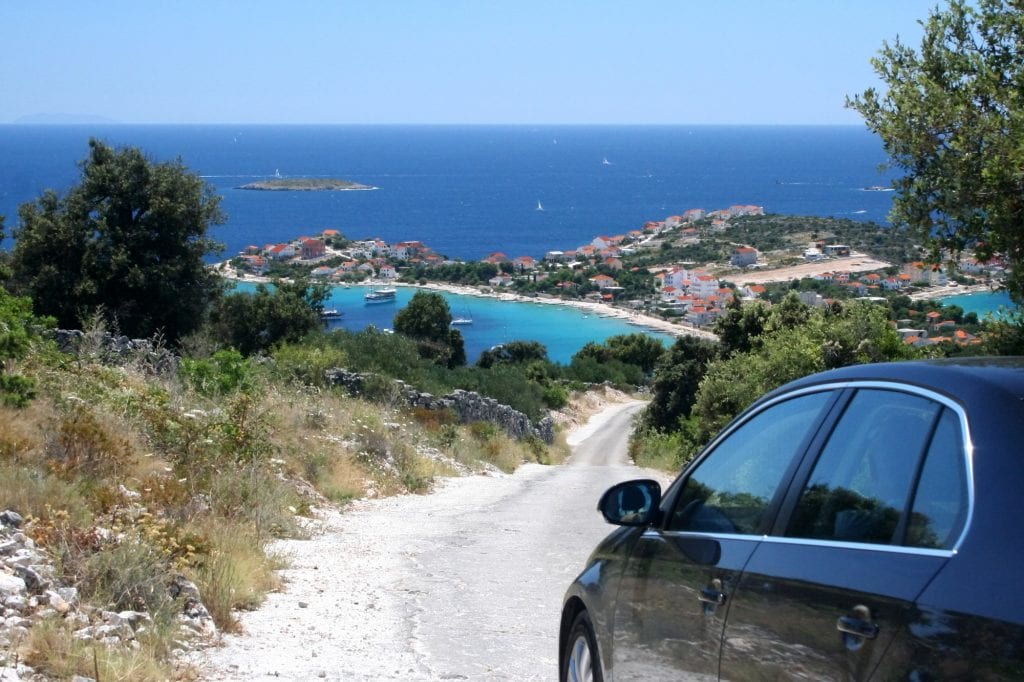 A car about to drive down a dirt road in Croatia. In the distance you see a coastal town with a bright white beach against the bright blue water.