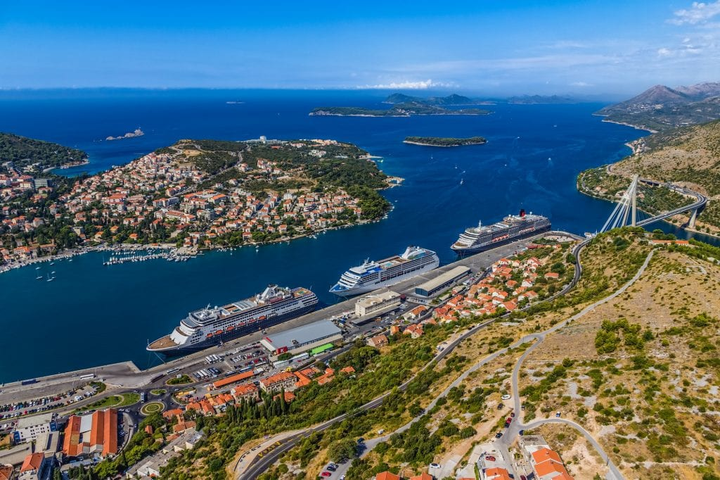 An aerial view of Gruz Harbor in Dubrovnik seen from the top of a mountain. You see three GIANT cruise ships parked in a line. In the background, you see the Kornati Islands poking out of the ocean.