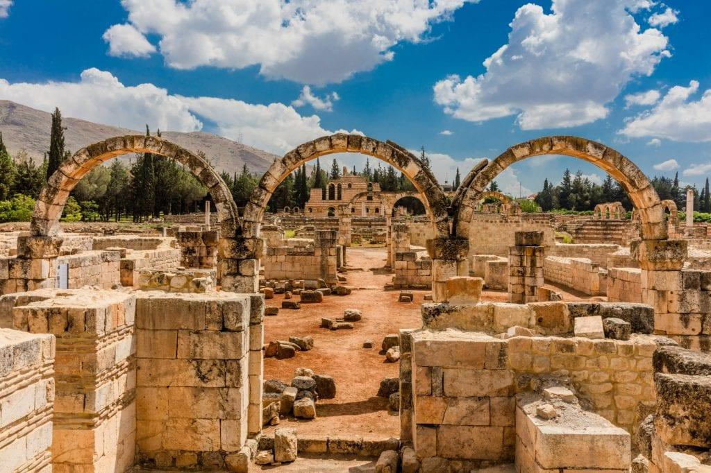 Las ruinas de Anjar: ves edificios de piedra derruidos.  En el medio hay tres arcos de piedra, cada uno hecho de una sola hilera de piedras.  Al fondo, montañas (y más allá, Siria).