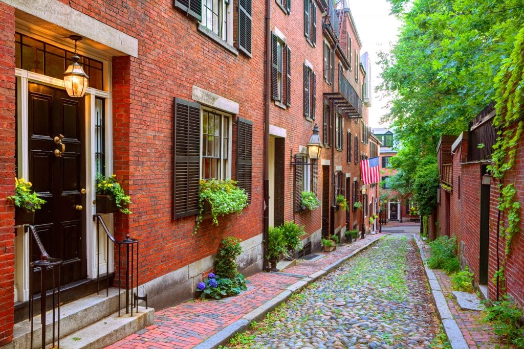 A small cobblestone street in the Beacon Hill neighborhood, edged with historic red brick buildings.