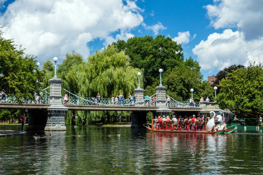 A small suspension bridge over a pond in the Boston Public Garden, a swan boat with a wooden swan in the front and people sitting on red benches, floating down the pond.