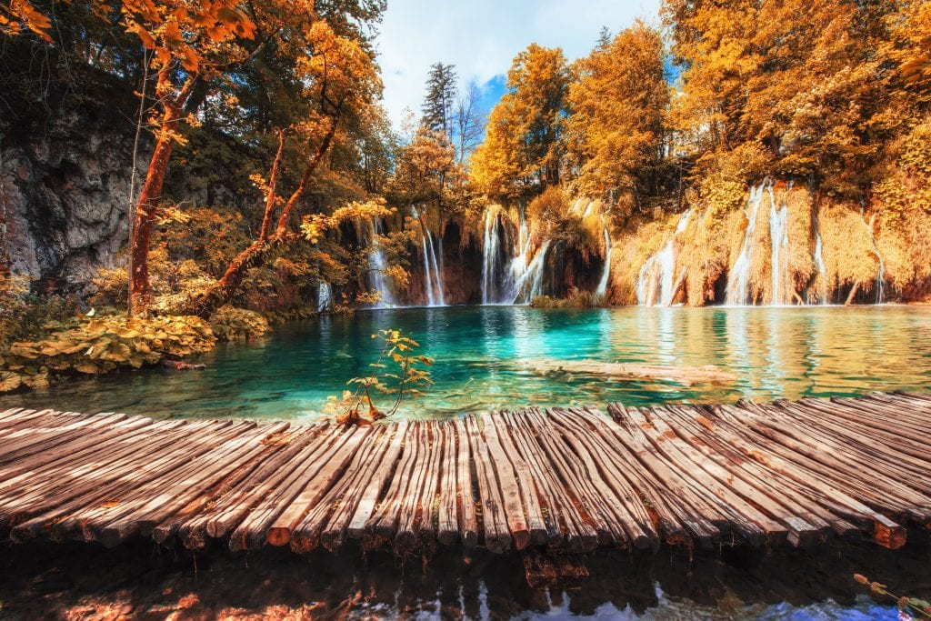 A wooden walkway on the clear teal Plitvice Lakes, surrounded by orange and red trees, waterfalls flowing through the vegetation.