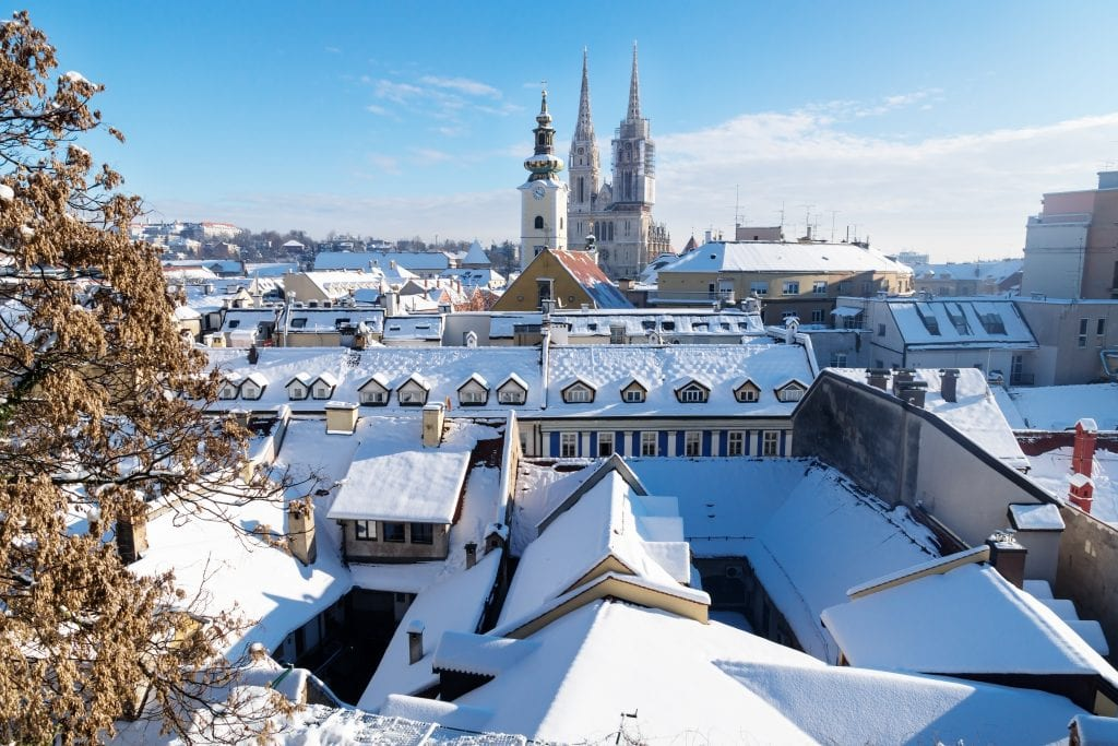Snow-covered roofs in Zagreb underneath a bright blue sky. In the middle you see two church towers and a clock tower, all covered with snow.