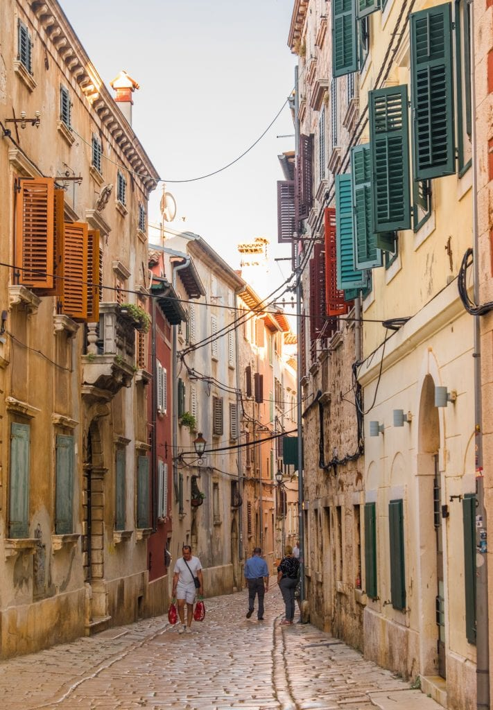 A narrow cobblestoned street in Rovinj. The buildings have green and red shutters and laundry hangs out of some buildings. It looks a lot like Italy.