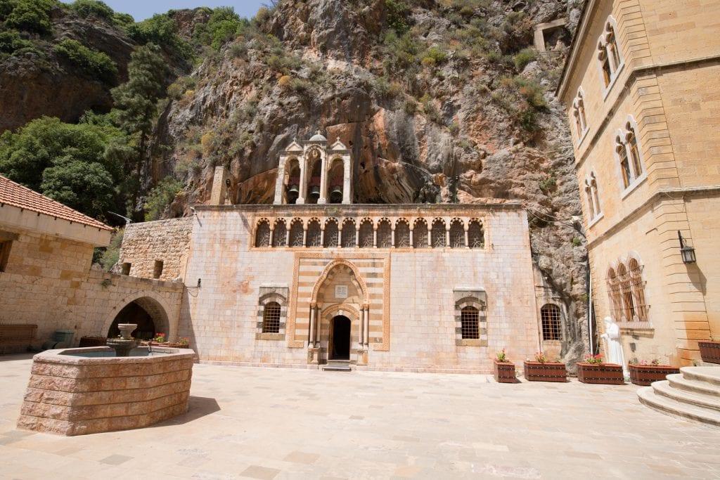 Frente a un gran muro de piedra, ves una iglesia color arena, con ventanas y puertas arqueadas talladas en ella.  Parece que está creciendo de la piedra.