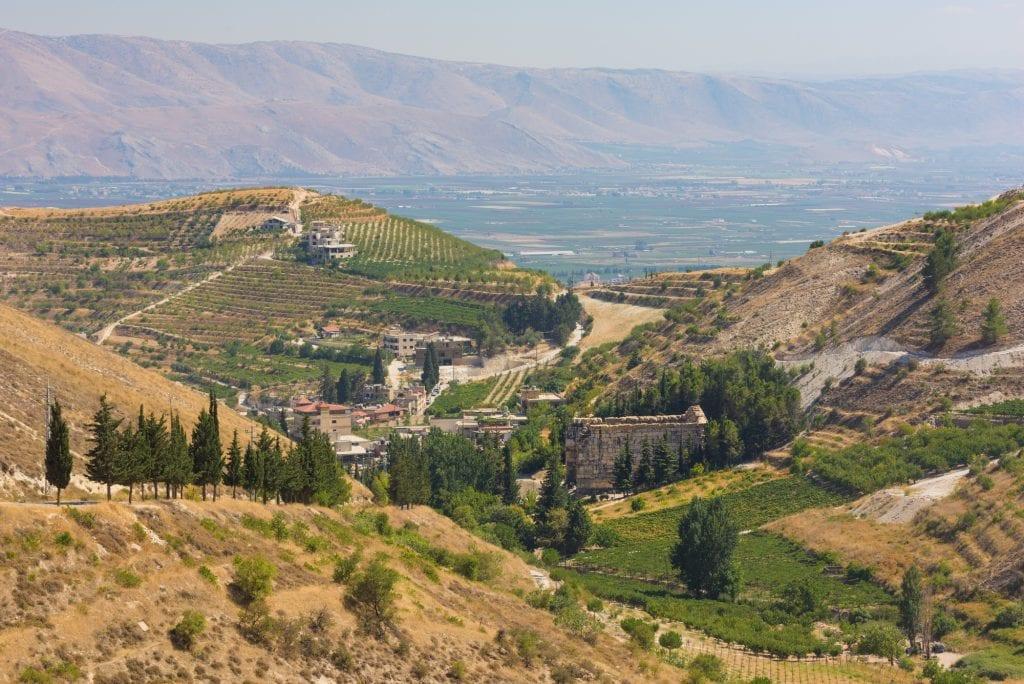 Un paisaje montañoso en el Líbano.  En las pequeñas colinas hay viñedos en terrazas y pequeñas construcciones;  a lo lejos, ves una montaña empinada.