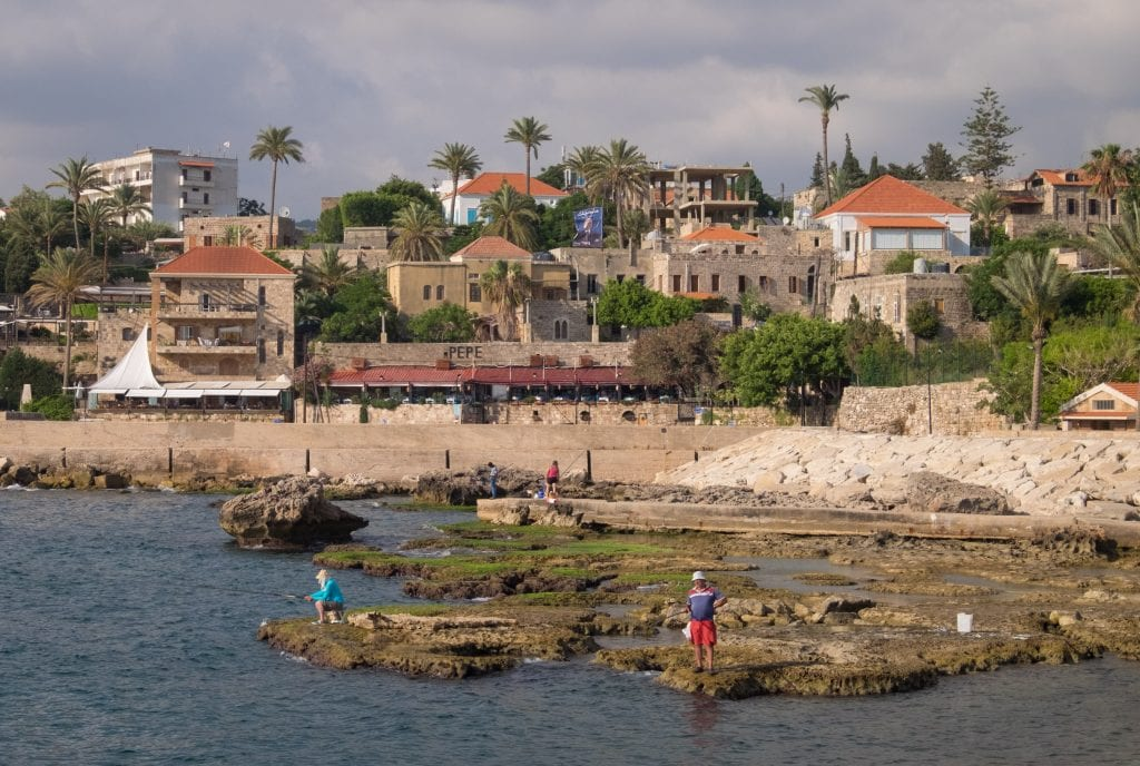 The seaside village of Byblos, Lebanon. Along the rocky edge are people standing in the water and fishing; in the background are small stone buildings on shore and lots of palm trees.