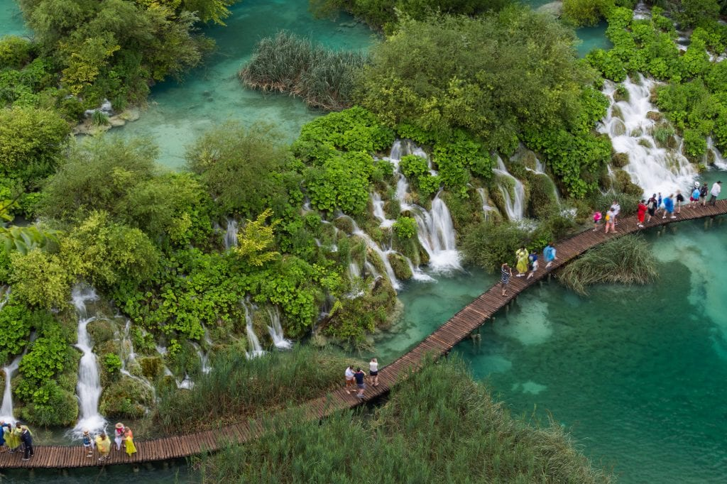 An aerial shot of the Plitvice Lakes. A wooden platform with people walking on it sneaks through the clear teal lakes. Next to the platform are something like 20 mini waterfalls, all bursting through the trees and bushes.
